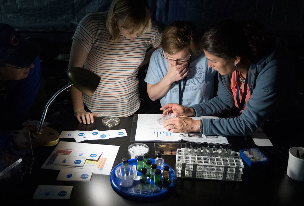Kiki Contreras (from left), of Seattle Wash., Cal Pumala, of Cameron Wi., and Angela Gospodarek, of Gorham, Me., work together during an escape room activity Monday, June 5. The scholars were split into teams and used the microscopes they made earlier in the day to solve clues. (Photo by Brook Joyner)